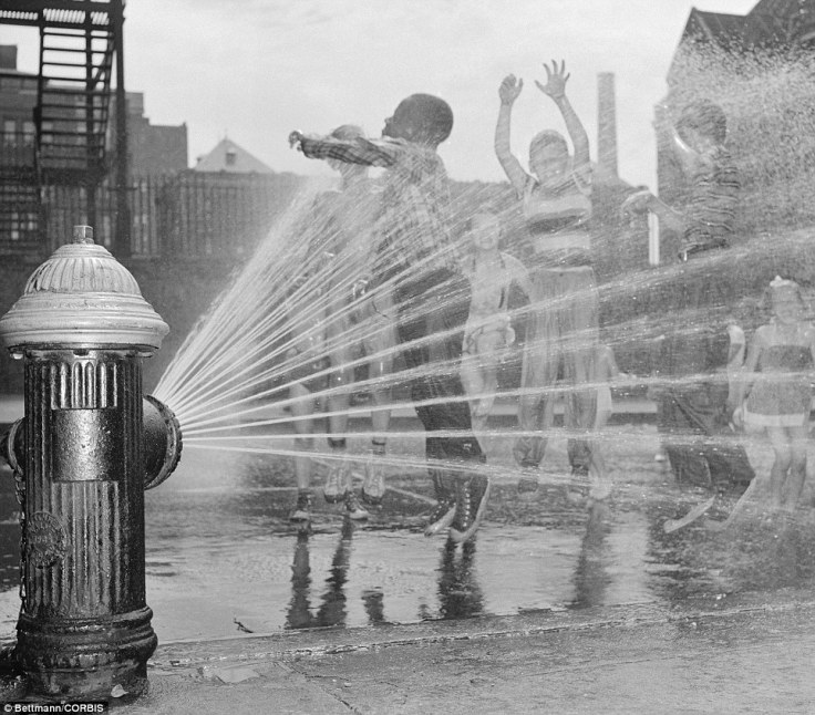 kids playing in fire hydrant in the heat