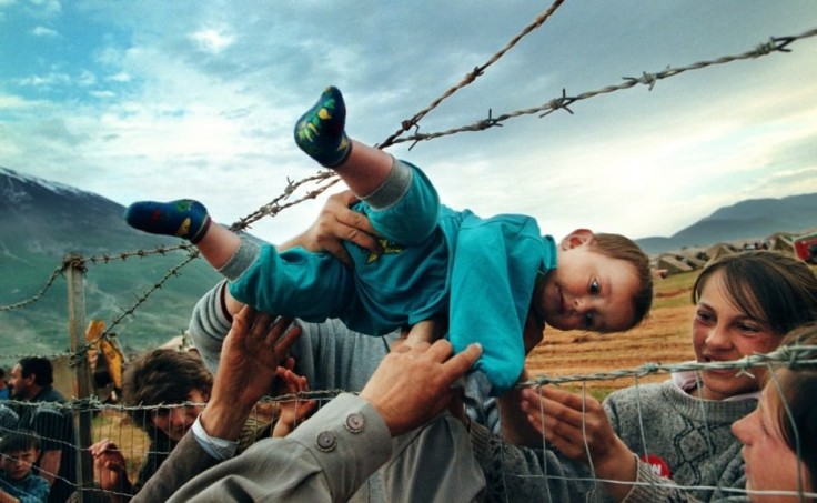 Agim-Shala-passed-through-barbed-wire-fence-to-his-family-at-Kosovo-refugee-camp